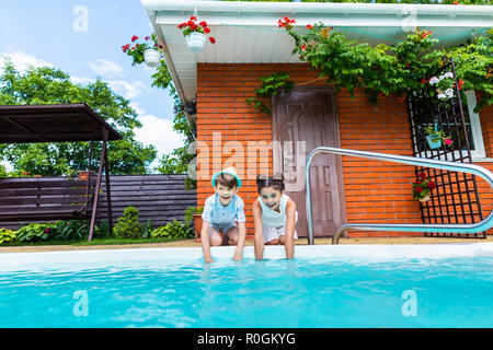 little siblings sitting near swimming pool on summer day - Stock Photo