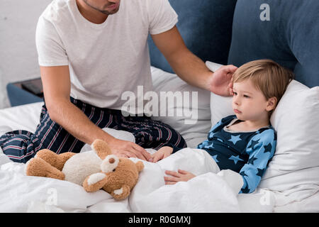 cropped shot of young father checking sons temperature with hand while he lying in bed - Stock Photo