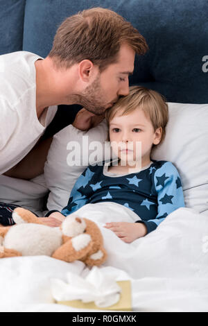 father checking sons temperature with lips while he lying in bed - Stock Photo