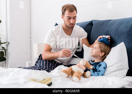 father checking sons temperature with electric thermometer and holding ice pack on his head in bed - Stock Photo