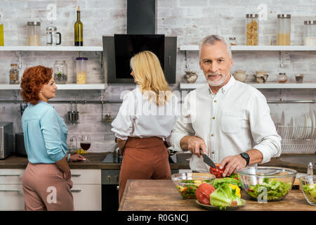 handsome man preparing salad for dinner at home, women talking with wine - Stock Photo