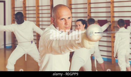 Portrait of focused man wearing fencing uniform practicing with foil in gym - Stock Photo