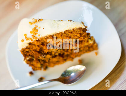Piece of delicious carrot cake with egg white frosting served on white plate - Stock Photo