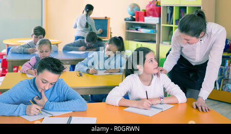 Woman teacher helping drawing to group kids 9-10 years old at class. Focus on boy - Stock Photo
