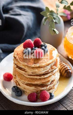 Oat Pancakes With Blueberries, Raspberries And Honey For Breakfast On White Plate On Wooden Table. Selective focus - Stock Photo
