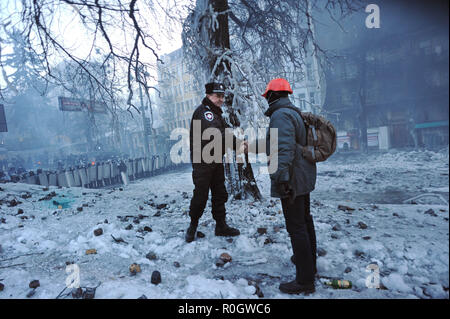 January 25, 2014 - Kiev, Ukraine: A police officer and a protester shake hands after a brief talk in the no man's land as thousands of angry anti-government protesters face riot police from their barricades near Independence Square. This part of Kiev's city center was devastated after heavy clashes between protesters burning tires and police forces using water cannon in freezing temperatures Protesters have built barricades to prevent police from storming Maidan, Kiev's independence square, the epicenter of the anti-government revolt. Des barricades sont erigees dans un climat glacial dans le  - Stock Photo