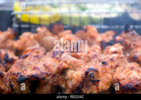 Skewers with roasted chiken meat and vegetables on the hot grill closeup, weekend barbecue - Stock Photo