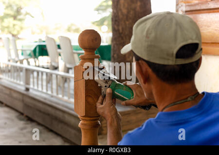 Asian worker cut wooden pole with grinding machine outdoor. - Stock Photo
