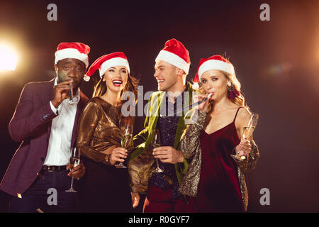 6dd8921c312c7 ... excited multicultural friends in santa hats with champagne glasses -  Stock Photo