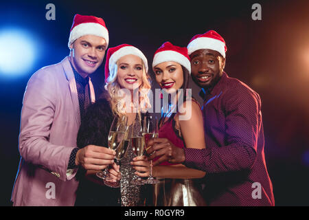 94f224917837e ... multicultural glamorous friends in santa hats clinking with champagne  glasses on new year party - Stock
