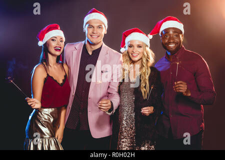 f59f1ad481ff3 ... holding champagne glasses · multiethnic friends in santa hats  celebrating new year with bengal lights - Stock Photo