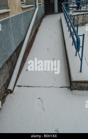Footprints in the snow on the ramp installed for the movement of people with disabilities at any time of the year - Stock Photo