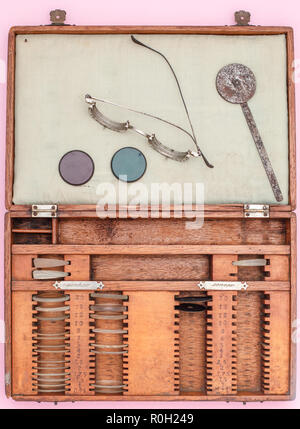 A wooden case of  old trial lenses set for a phoropter used for eye exam , circa 1940, top view - Stock Photo