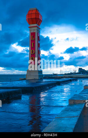The Art Deco Lido signpost on the seafront in Margate. On a dark rainy evening the puddles on the roof of the lido reflect the sign. Also in B&W. - Stock Photo