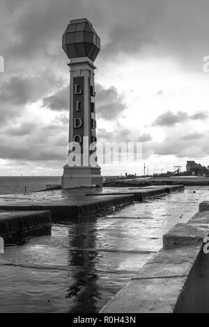 The Art Deco Lido signpost on the seafront in Margate. On a dark rainy evening the puddles on the roof of the lido reflect the sign. Also in colour. - Stock Photo