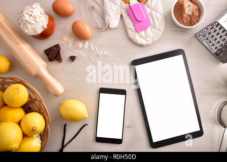 Pastry ingredients on a white wooden table and mobile devices. Concept of recipes in digital book. Horizontal composition. Top view - Stock Photo