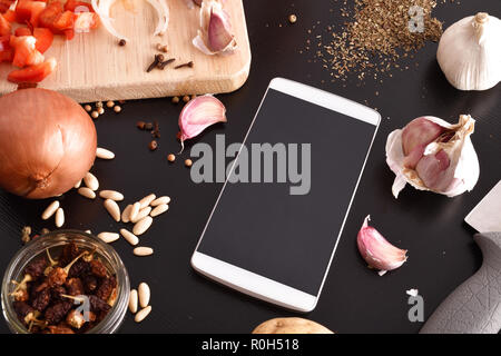 Preparation of vegetables on black wooden table with white mobile. Concept of recipes in digital book. Horizontal composition. Top elevated view - Stock Photo