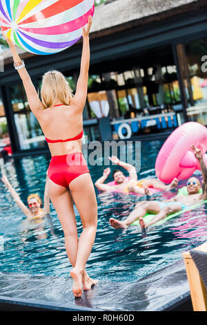 rear view of young woman standing with swimming ball while her friends having fun in swimming pool - Stock Photo