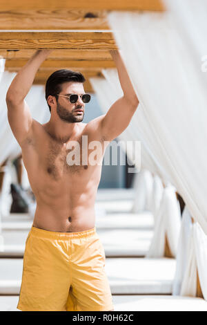handsome shirtless man in sunglasses standing near sun loungers - Stock Photo