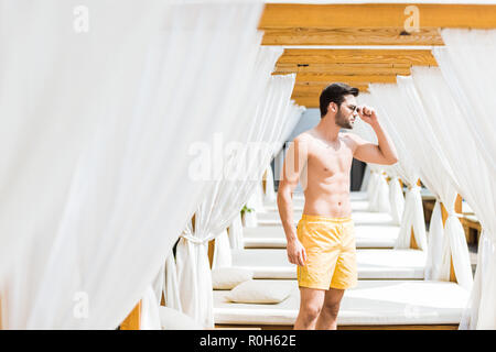 handsome shirtless man in sunglasses standing near sun loungers and looking away - Stock Photo