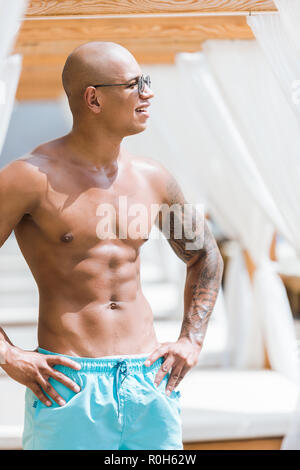 shirtless tattooed muscular man standing near sun loungers and looking away - Stock Photo