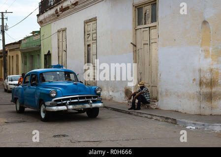 Man sitting on street corner as a vintage car passes - Stock Photo