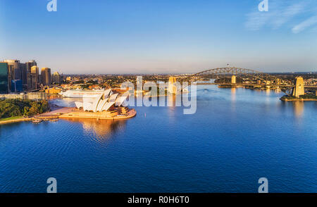 Calm Sydney harbour in early morning hour with soft sun light on massive steel arch of the Sydney Harbour bridge connecting city CBD towers and waterf - Stock Photo