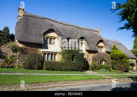 View of traditional Cotswold stone thatched cottage along Westington in autumn afternoon sunshine taken from public footpath - Stock Photo
