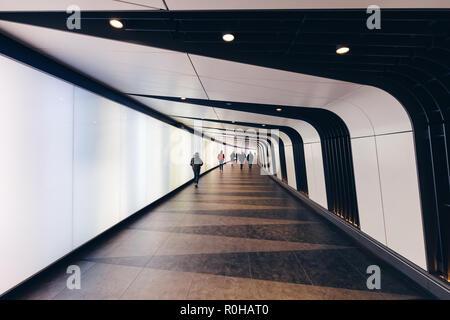 LONDON - OCTOBER 31, 2018: People walking in futuristic modern sci-fi moody tunnel background in city London - Stock Photo