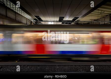 Speeding train arriving at platform on London underground tube station - Stock Photo