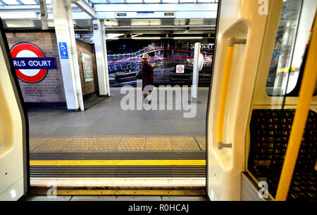 Woman with her mobile phone on the platform of Earl's Court underground station, London, England, UK. - Stock Photo
