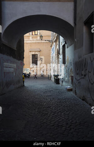 Archway in Rome, Italy with two people passing by - Stock Photo