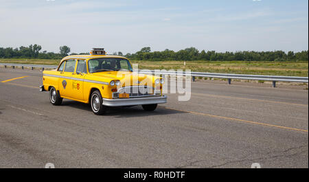 Yellow Checker Taxi Cab on an empty road. The Checker Taxi Cab produced by the Checker Motors Corporation was used by an American taxi company called  - Stock Photo