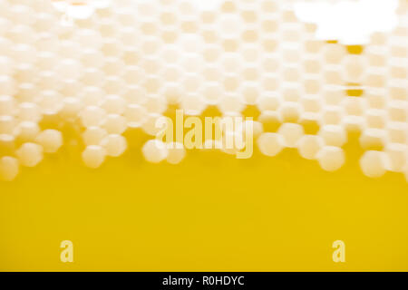 The light passes through the mesh structure, forming blurred hexagonal spots. Abstract background. - Stock Photo