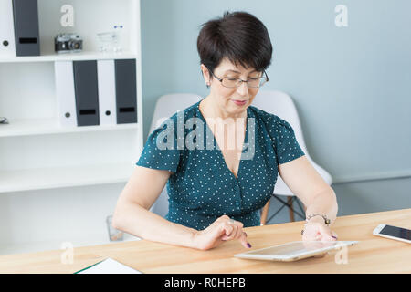 Business and people concept - middle aged confident woman is working with tablet in office - Stock Photo