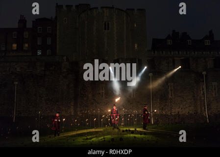 London, UK.  5 November 2018. Yeoman Warders, former servicemen and women, ceremonially light the first flame followed by volunteers proceeding to light the rest of the installation, gradually creating a circle of light.   A new installation by designer Tom Piper called 'Beyond the Deepening Shadow: The Tower Remembers', is open for the public to view at the Tower of London until Armistice Day 2018.  The moat is filled with thousands of individual flames commemorating the centenary of the end of the First World War. Credit: Stephen Chung/Alamy Live News - Stock Photo