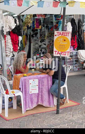 A tarot card reader and her client at the Carmel Market in Tel Aviv, Israel. Her sign is in three languages. - Stock Photo