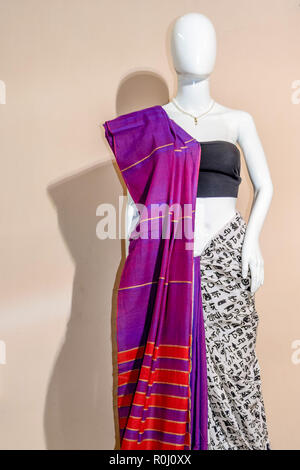 A traditional indian colorful silk saree displayed for sale. Selective focus on model face - Stock Photo