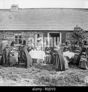 Alate Victorian vintage black and white photograph, showing a group of women dressed in traditional Welsh costume, outside a small house. Some are drinking tea, some are doing needlework. The traditional Welsh hat is very much shown. - Stock Photo