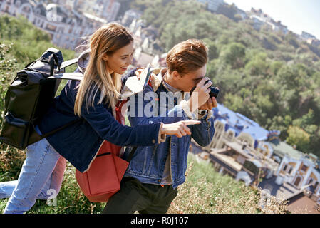 Young couple of travel bloggers are trying to make a photo at unfamiliar place - Stock Photo