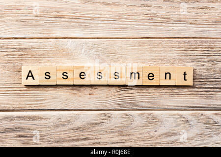 assessment word written on wood block. assessment text on table, concept. - Stock Photo