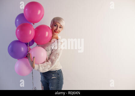Portrait of a beautiful woman with balloons and holiday gifts - Stock Photo
