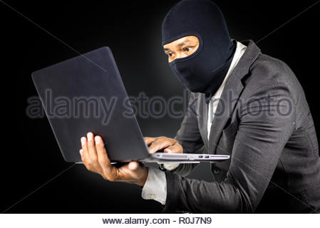 Data theft, Anonymous hacker with laptop on white isolated background, Cyber security concept - Stock Photo