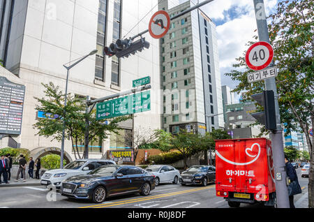 A busy road junction in Gangnam, Seoul, South Korea. Signs hanging overhead help drivers navigate. - Stock Photo
