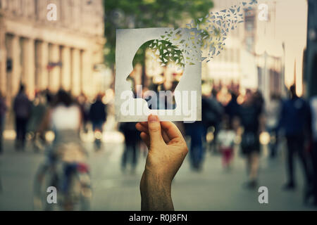 Hand holding a paper sheet with human head icon broken into pieces over a crowded street background. Concept of memory loss and dementia disease. Alzh - Stock Photo