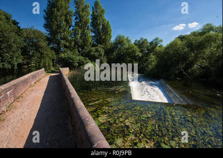 A waterfall and a bridge on Grand Union Canal, United Kingdom - Stock Photo