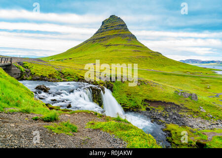 View of Kirkjufellsfoss and Kirkjufell mountain at Grundarfjordur Village in the north of the Snaefellsnes peninsula in the west of Iceland - Stock Photo