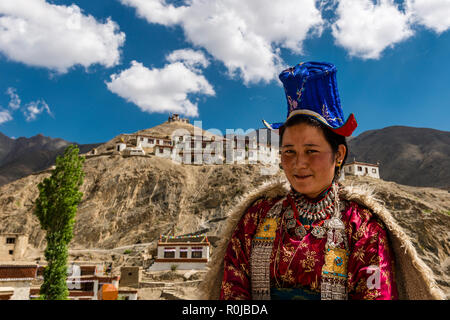 A ladakhi woman is displaying her traditional dress, Lamayuru Gompa and blue sky with white clouds in the background - Stock Photo