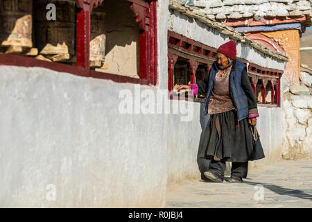 An old ladakhi woman is walking around Lamayuru Gompa, the oldest and largest existing monastery in Ladakh, turning prayer wheels for religeous reason - Stock Photo