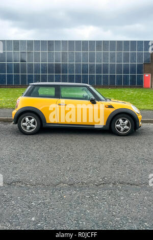 yellow BMW Mini 3 door car with a contrasting black roof parked at the side of the road in front of a building covered in solar panels - Stock Photo
